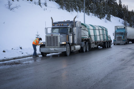 Photo of trucker checking headlight of rig pulled off highway in winter