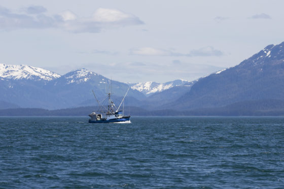 Photo of a fishing boat with snow-covered mountains in the background