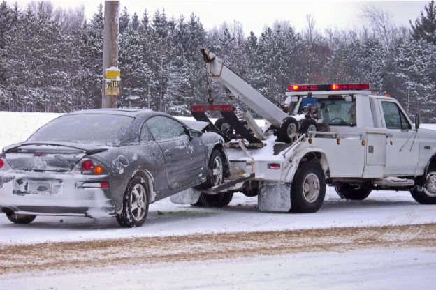 Photo of a towtruck with car winched up behind it, in snow