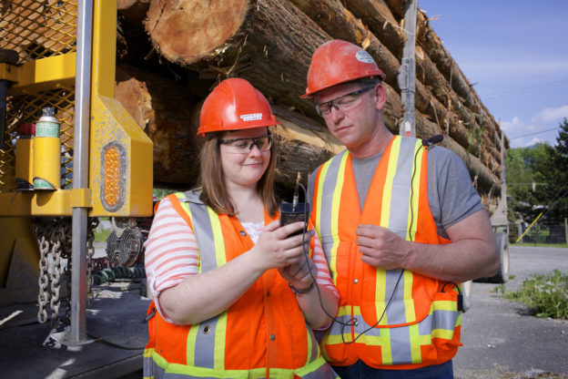 Photo of woman and man in safety vests and hard hats with loaded log transporter behind them