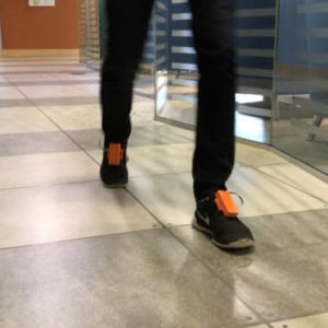 Photo of person's feet wearing shoes outfitted with outfitted with insoles that measure weight-bearing activity