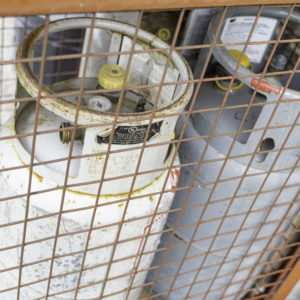 Photo of two propane tanks stored in a wire cage
