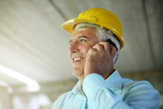 Photo of man wearing a yellow hardhat, talking on cellphone