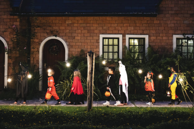 Photo of children in Halloween costumes out trick-or-treating