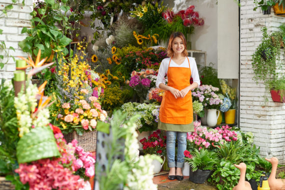Photo of woman in orange apron, standing in her flower shop, surrounded by plants and blooms