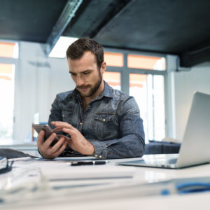 Photo of man texting sitting at desk with laptop open