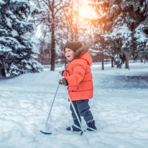 Photo of young child in winter gear, using skis on flat ground covered with snow, and nearby trees covered in snow