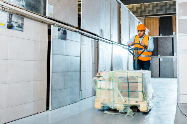 Photo of a worker using a powered pallet jack in a warehouse