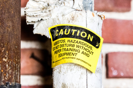 Photo of asbestos-containing thermal pipe insulation labelled by an inspector