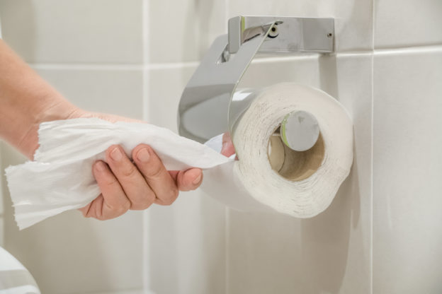 Photo of a hand pulling toilet paper from a roll on a wall next to an unseen toilet