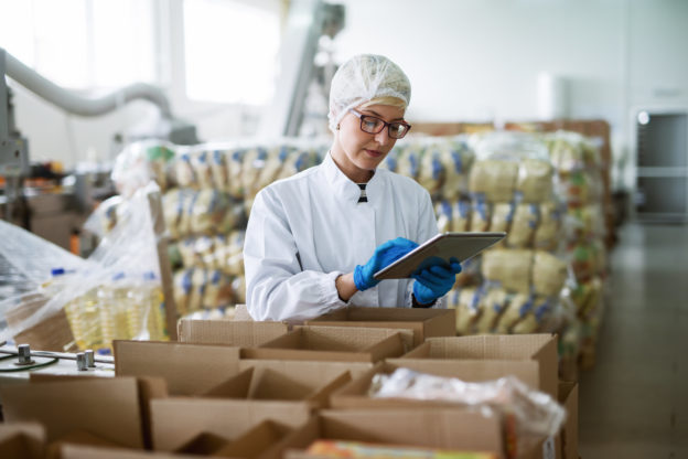 Photo of worker using tablet for checking boxes in food factory