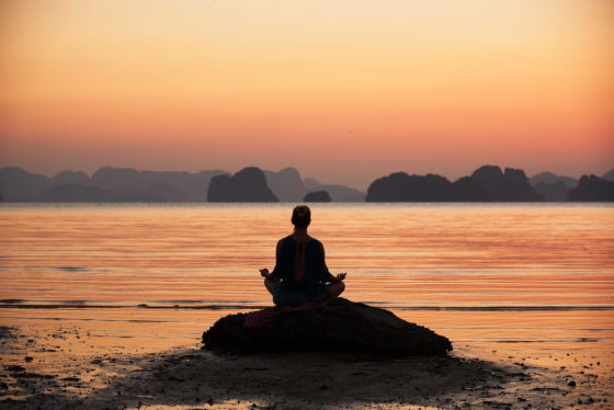 Photo of a figure meditating on a rock by the ocean during an orange sunrise