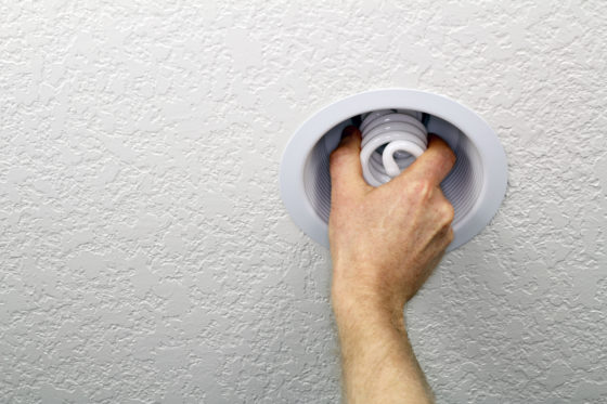 Photo of a hand installing spiral compact fluorescent lightbulb in a recessed white ceiling fixture