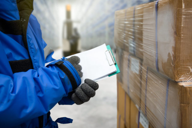 Photo of worker with clipboard in freezing room of a warehouse