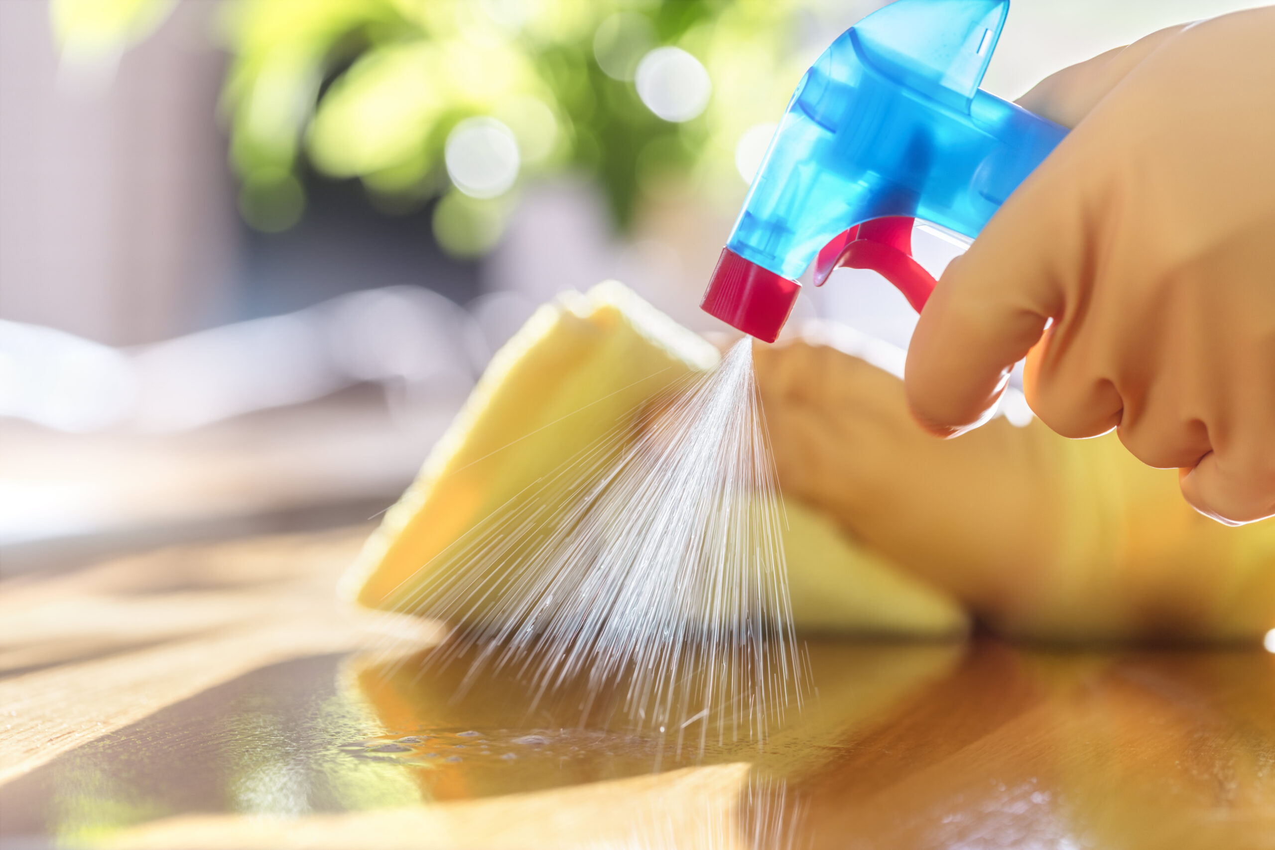 Photo of cleaning surface with hands in yellow rubber gloves holding spray bottle and sponge