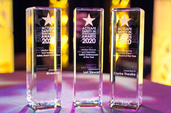 Photo of three Actsafe Safety in Entertainment awards, glass pillars against a backdrop of yellow and purple lights