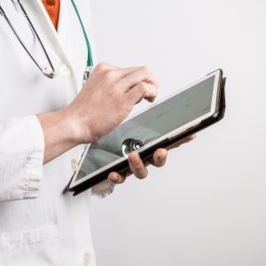 Photo of doctor in white coat using tablet