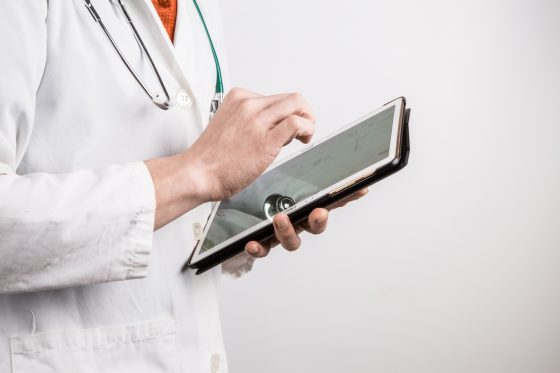 Photo of doctor in white coat holding tablet