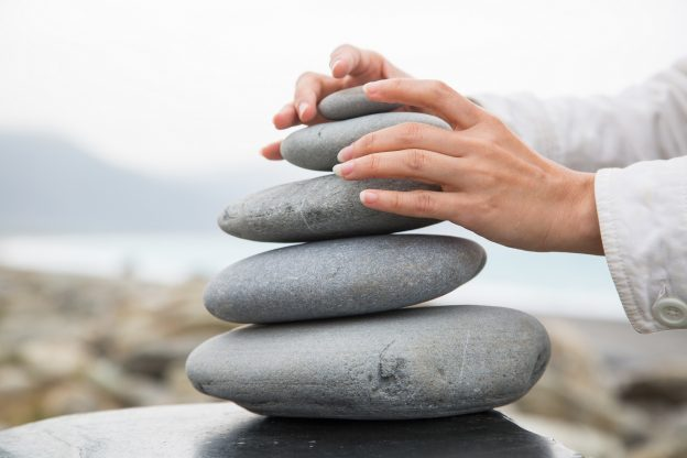 Photo of person's hands stacking stones into a balanced pyramid