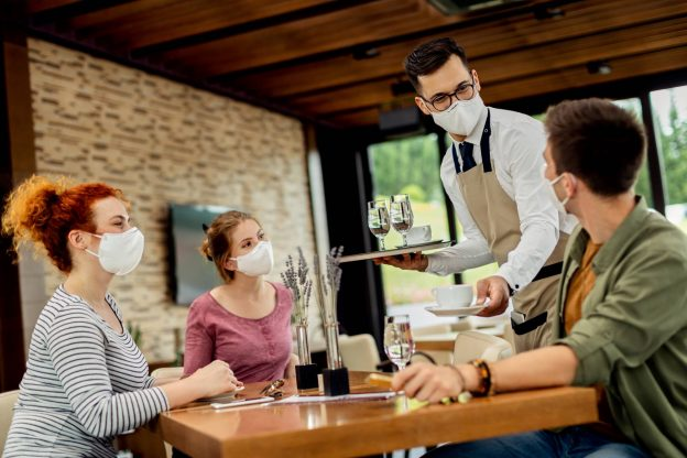 Photo of waiter serving coffee to group of friends while everyone one is wearing protective face mask due to COVID-19 epidemic.