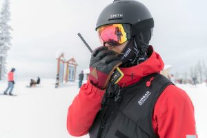 Photo of person working on snowy mountain, wearing cold weather gear and talking into a two-way radio