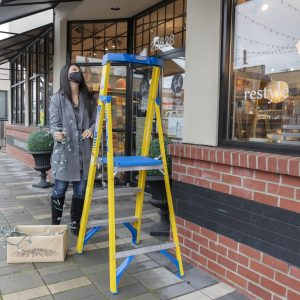 Photo of person wearing face mask to protect against COVID-19 and about to climb ladder to put up winter holiday lights