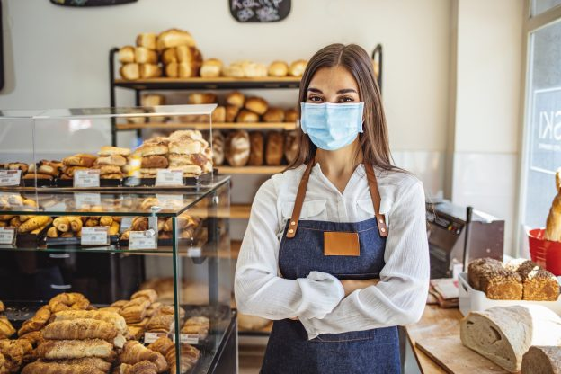 Photo of owner of bakery shop, wearing a mask to comply with health order requirement against COVID-19. .