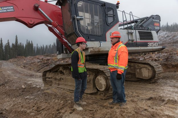 Photo of young worker interacting with older worker in front of a feller buncher