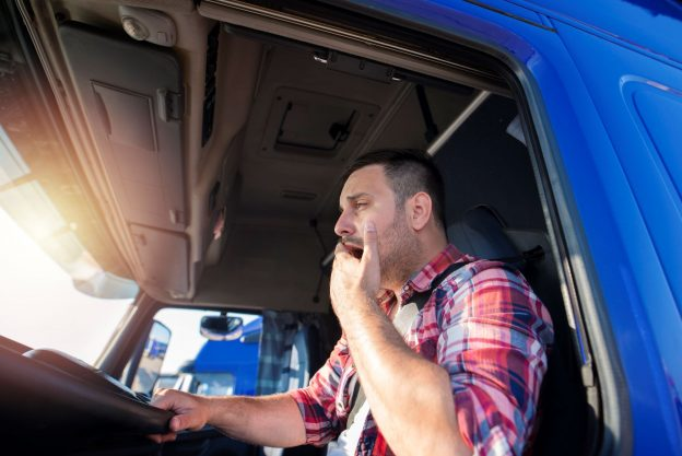 Photo of fatigued truck driver yawning in the driver's seat.