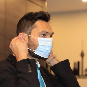 Photo of business man putting on reusable face mask