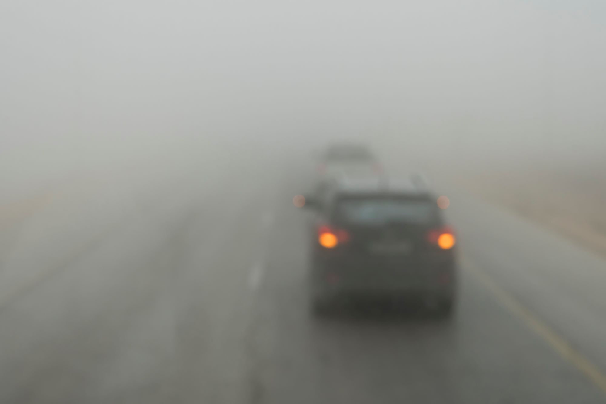 Photo of cars driving in dense smoke, with tail lights on