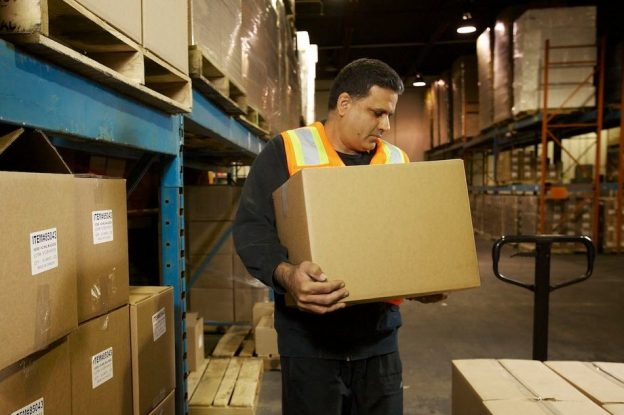 Photo of a worker wearing a high visibility vest and holding a cardboard box in warehouse