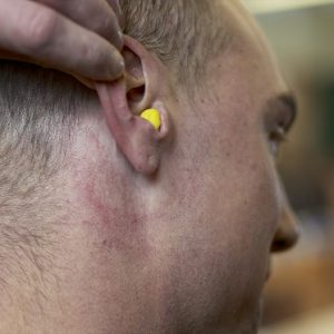 Photo of man pulling back right ear with hearing protection inserted