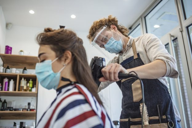 Photo of a hair stylist in a hair salon, wearing a mask and face shield, drying a customer's hair who is also wearing a mask.