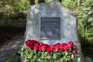 Photo of Day of Mourning monument for workers, with red roses placed in front.