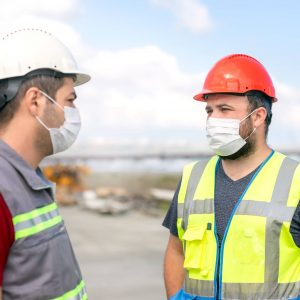 Photo of prime contractor and construction worker discussing and wearing masks to protect against COVID-19.
