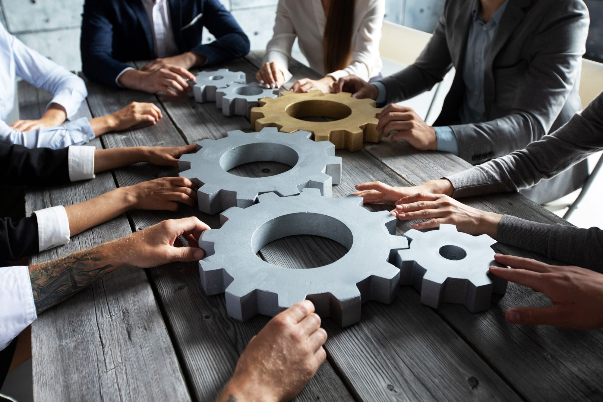 Photo of Group of business people joining together silver and golden colored gears on table at workplace.
