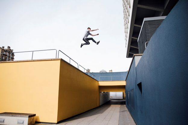 Photo of stunt performer jumping between tall buildings in the city.