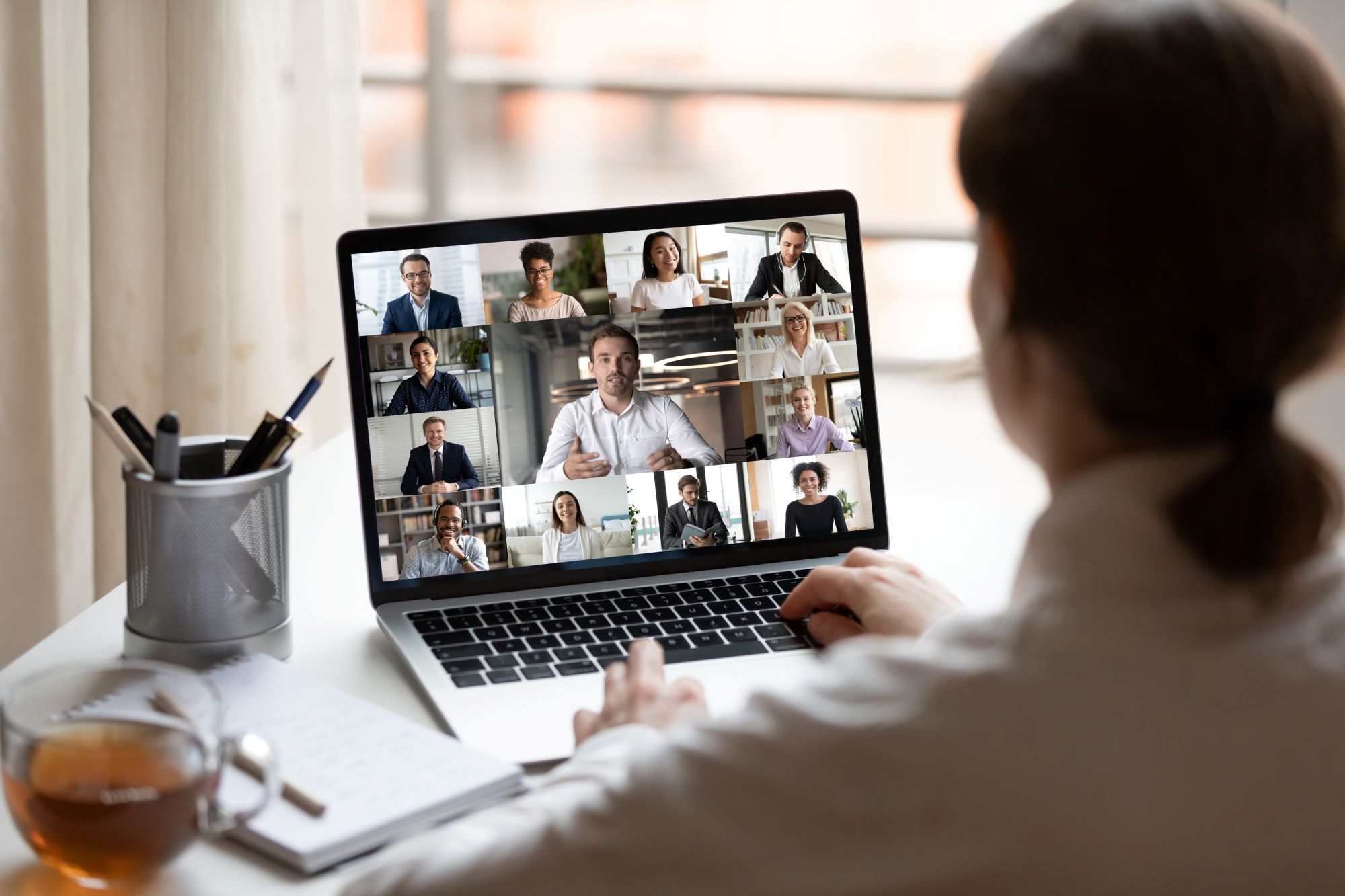 Photo of business woman seated at desk, looking at laptop of various people during a virtual meeting