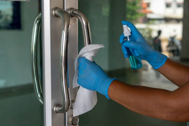 Photo of person wearing gloves while cleaning and disinfecting a door handle
