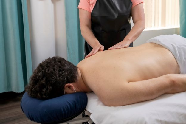 Photo of man wearing mask and getting massage by therapist