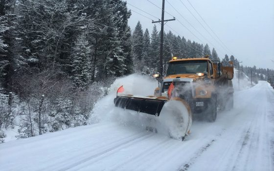 Photo of a snowplow plowing snow on the road in winter
