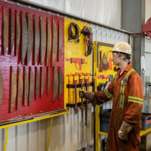 Photo of worker taking a tool from an organized wall of tools in manufacturing facility.