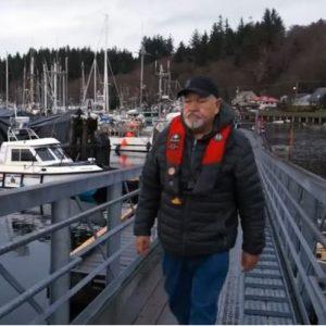 Photo of man wearing PFD walking up ramp on a dock