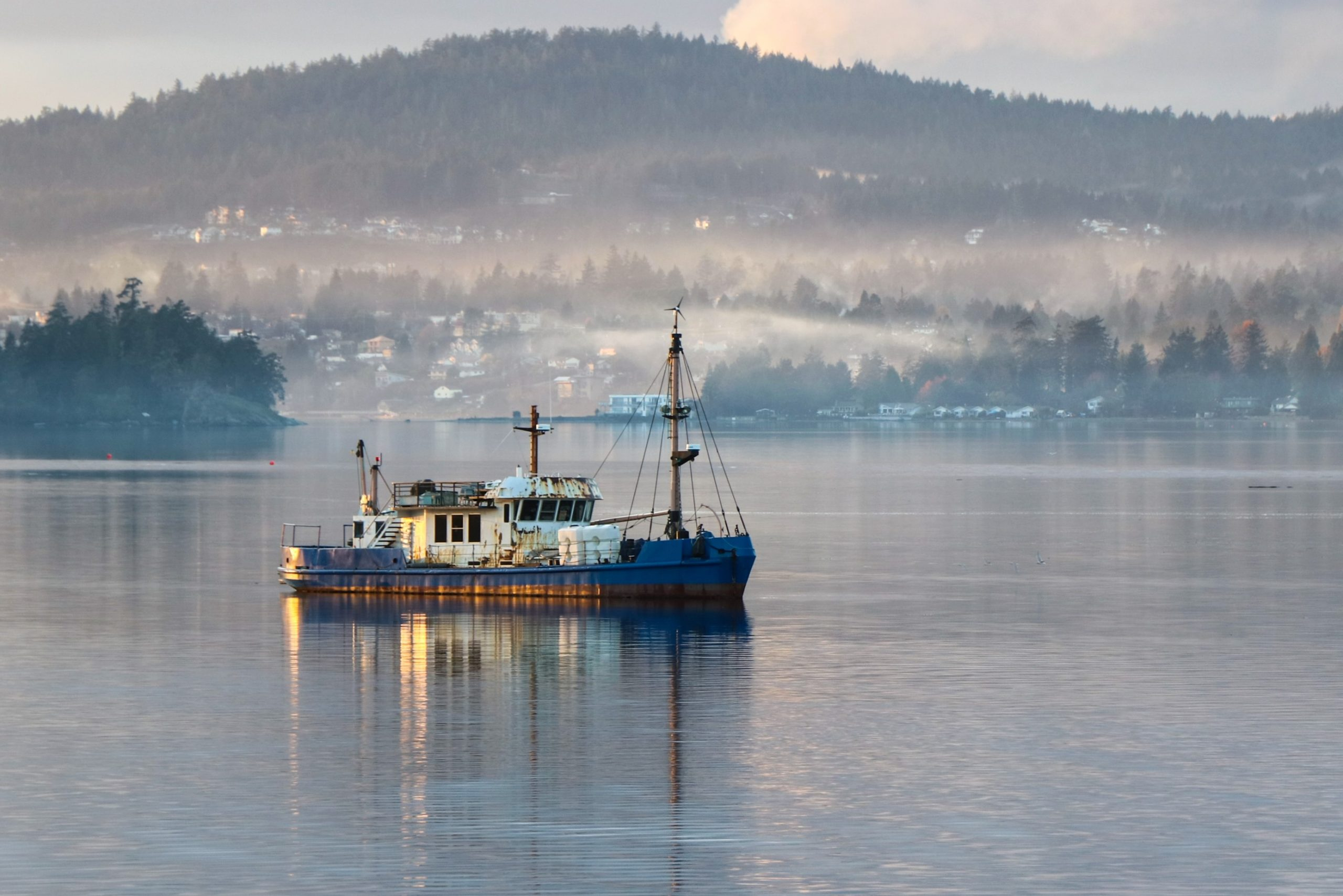 Photo of Trawler vessel at anchor in a calm bay at Roche Cove, Sooke, British Columbia.