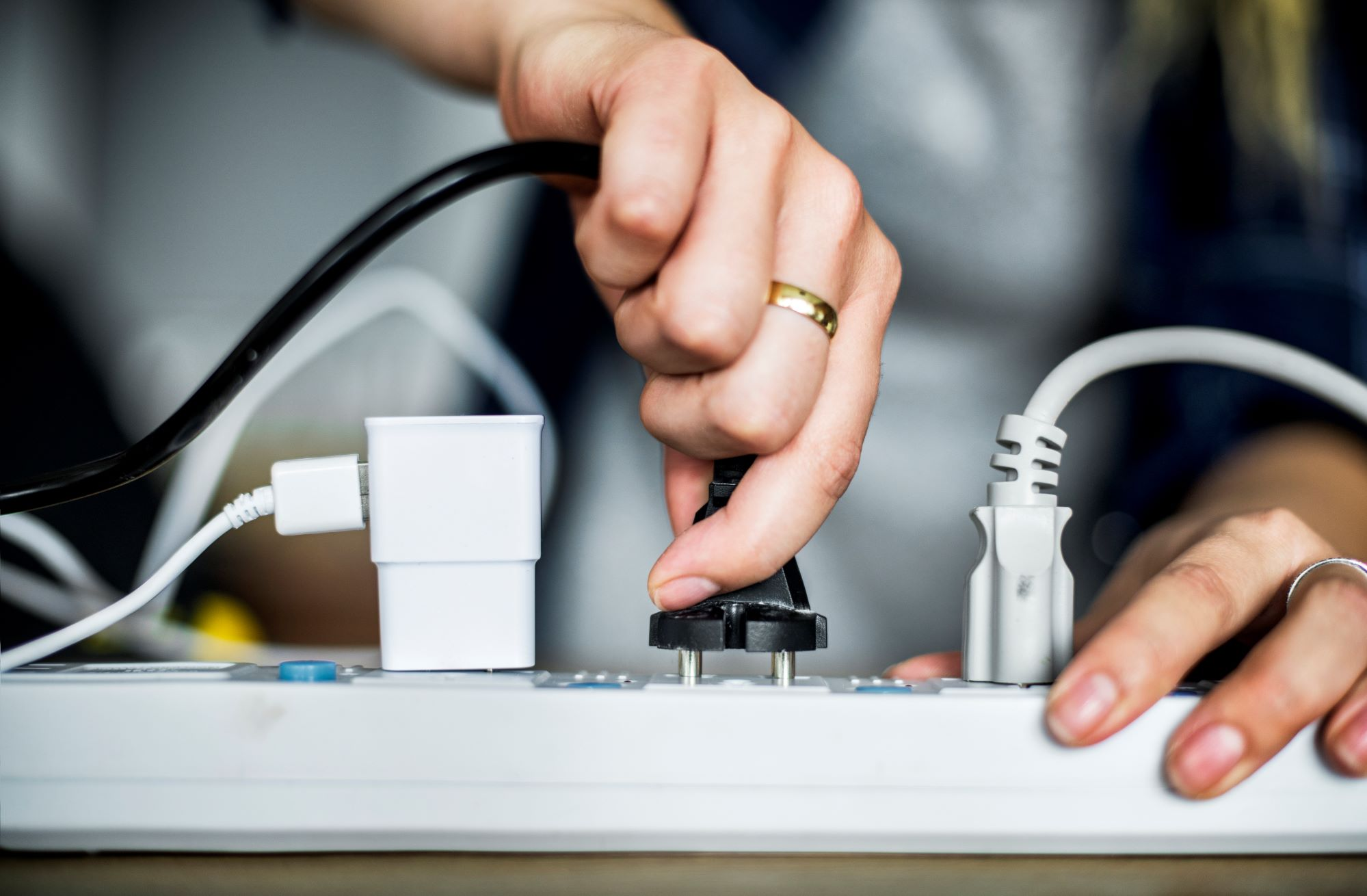Photo of a woman plugging a wire into an electric power bar.