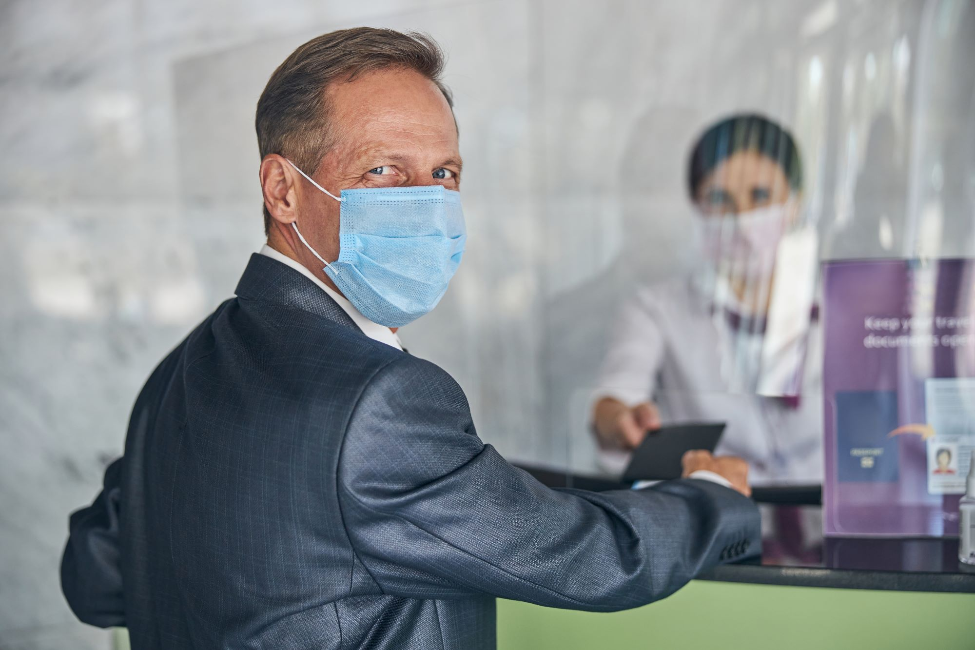 Happy man in suit gives documents to woman at hotel registration desk while wearing masks.