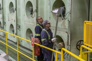 Photo of two workers at Domtar Kamloops Mill at the pulp dryer area.