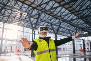 Photo of engineer using virtual reality goggles outdoors on construction site.