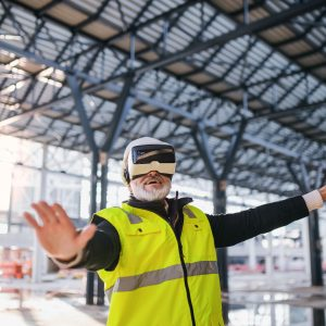 Photo of engineer using virtual reality goggles outdoors on construction site